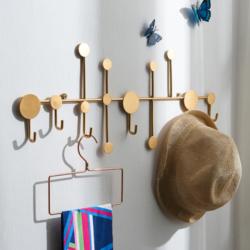 patère design dorée sur mur clair